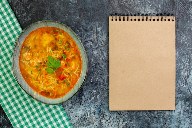 Vista dall'alto gustosa zuppa di vermicelli con blocco note sul tavolo grigio chiaro