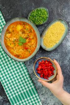 Vista dall'alto gustosa zuppa di vermicelli con condimenti sul tavolo grigio chiaro