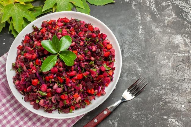Вид сверху вкусный салат из свеклы винегрет внутри тарелки на темной поверхности