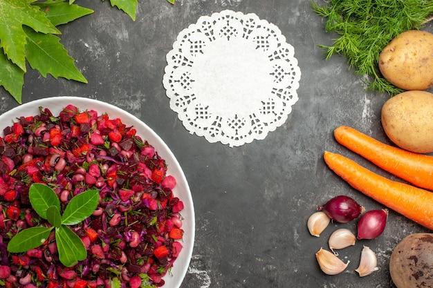 Vista dall'alto gustosa insalata di barbabietola vinaigrette con verdure sulla superficie scura
