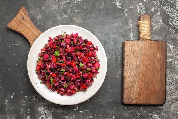Вид сверху вкусный салат винегрет с фасолью и свеклой на сером столе