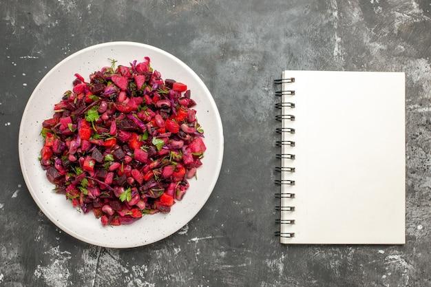 Вид сверху вкусный салат винегрет с фасолью и свеклой на серой поверхности