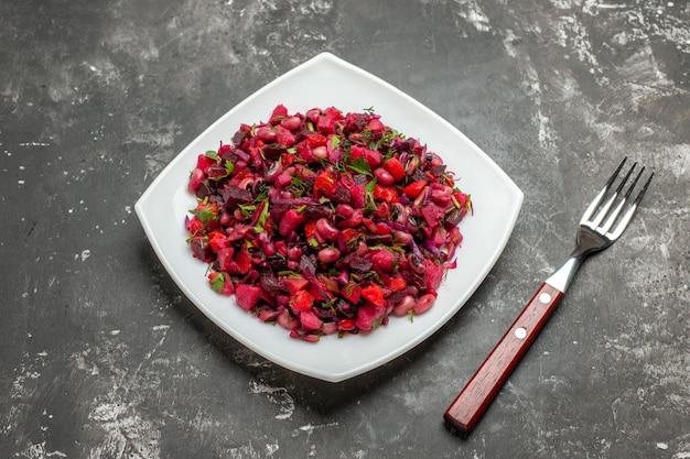 Vista dall'alto gustosa insalata vinaigrette con barbabietole e fagioli sulla scrivania grigia
