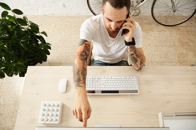 Top view of tattooed man shows something on display while speaking on phone on his working desktop in co-working center