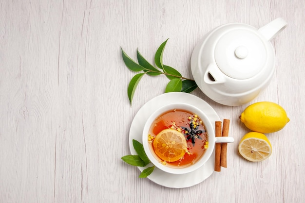 Вид сверху чай и корица чашка травяного чая палочки корицы на блюдце чайника с лимоном и листья на белом столе