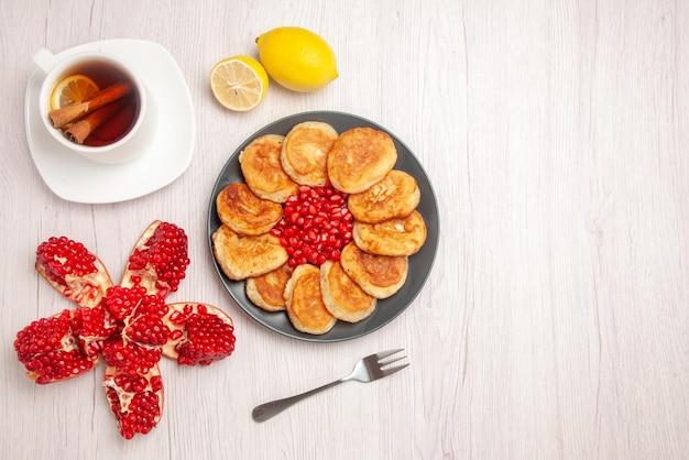 トップビューのお茶とパンケーキ赤いザクロとパンケーキと白い背景の上のフォークの種子のプレートの横にあるシナモンとレモンの皮をむいたザクロレモンとお茶のカップ
