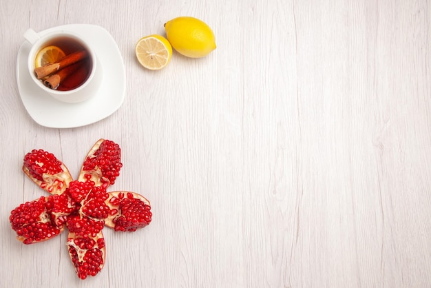 Вид сверху чай и блины чашка чая с корицей и долькой лимона очищенного граната и лимона на белом столе