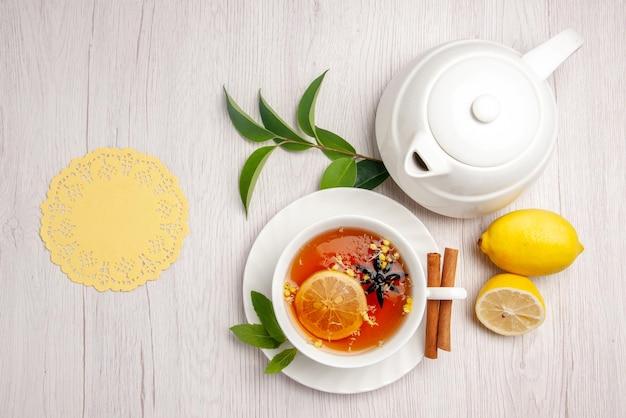 Vista dall'alto tè e cannella una tazza di tisana bastoncini di cannella sul piattino accanto alla teiera di limone centrino di pizzo e foglie sul tavolo bianco