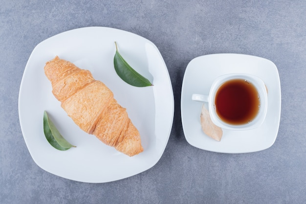 Top view of tea and croissants. classic breakfast.