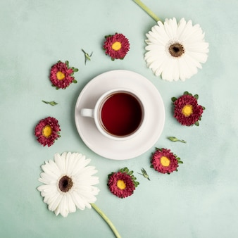 Top view tea cup of fruits and arrangement of daisies