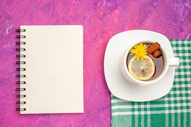 Tazza da tè vista dall'alto su asciugamano verde spogliato con quaderno su rosa