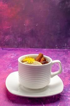 Tazza da tè vista dall'alto con ingredienti come cannella e limone su rosa in una forma verticale