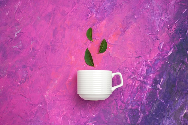 Top view tea cup with leaves on pink