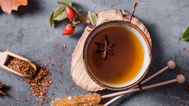 Top view tea in cup with star anise and crystallized sugar and cinnamon
