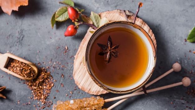 Vista dall'alto tè in tazza con anice stellato e zucchero cristallizzato e cannella