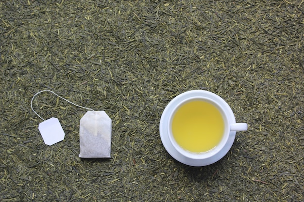 Top view of tea cup with tea bag on dried tea leaves background