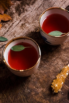 Top view tea in cups with crystallized sugar cane