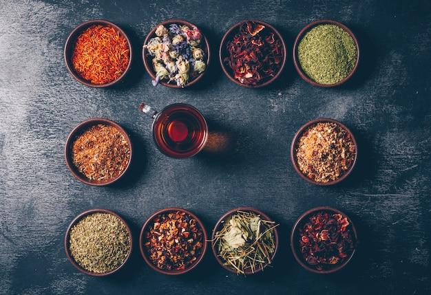 Vista dall'alto erbe del tè in ciotole con una tazza di tè su sfondo scuro con texture. orizzontale