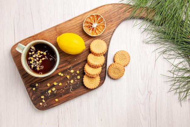 Vista dall'alto tè e limone una tazza di tè con biscotti alle erbe e limone sulla tavola della cucina e rami dell'albero di natale