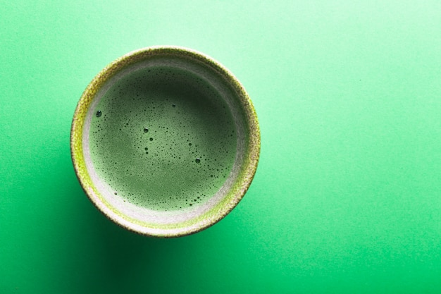 Top view of tea matcha in a bowl on greeen surface