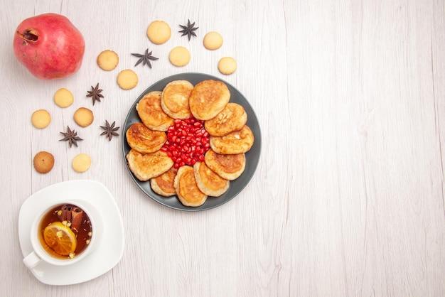 Vista dall'alto tè e frittelle piatto di frittelle con melograno una tazza di tisana al melograno e biscotti sul tavolo bianco