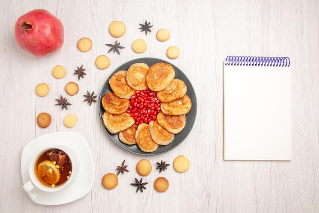 Top view tea and pancakes white notebook next to the dark plate of pancakes with pomegranate a cup of herbal tea pomegranate and cookies on the table