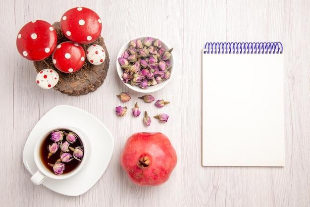 Vista dall'alto tè e melograno una tazza di tisana sul piattino accanto al quaderno bianco erbe di melograno e giocattoli di natale sul tavolo