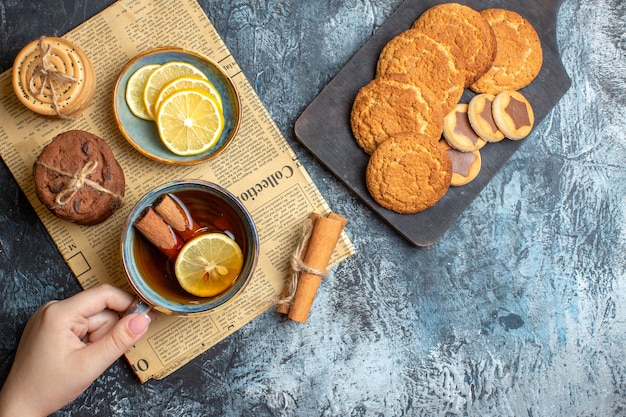 Top view of tea time with delicious cookies cinnamon lemon on an old newspaper