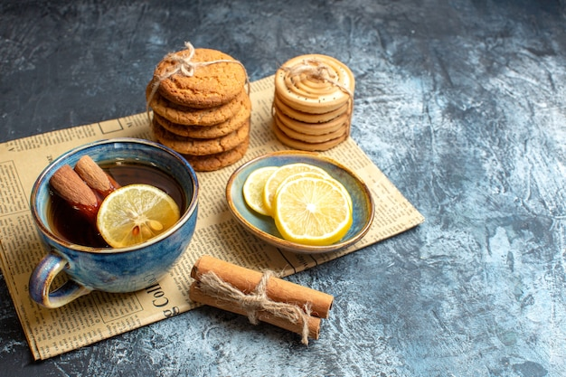 Top view of tea time with stacked delicious cookies cinnamon lemon on an old newspaper