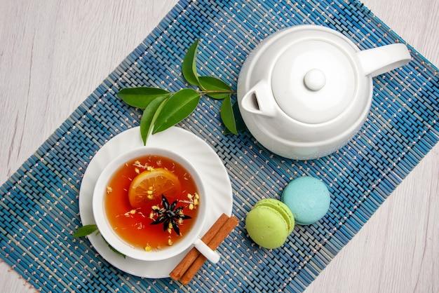 Вид сверху чай с лимоном белая чашка чая с лимоном и корицей рядом с чайником французские миндальные печенья и листья на сине-белой скатерти