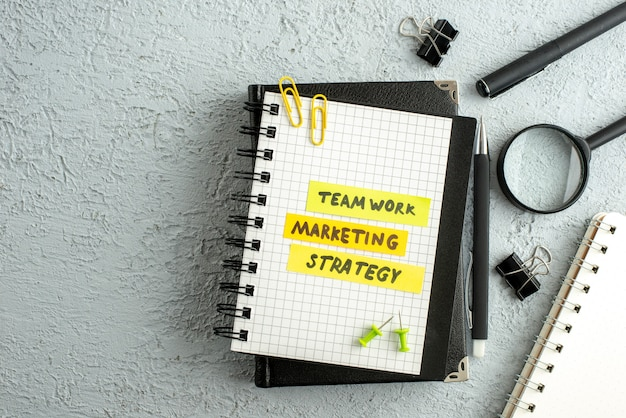 Top view of teamwork strategy marketing writings on coloured sheets on spiral notebook and book magnifying glass on gray sand background