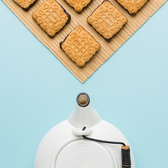 Top view teapot and biscuits on the table