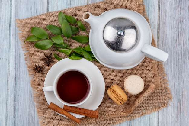 Top view teapot with a cup of tea cinnamon and macaroons on a beige napkin on a gray table
