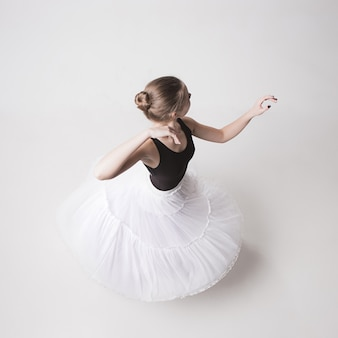 The top view of the teen ballerina on white studio background