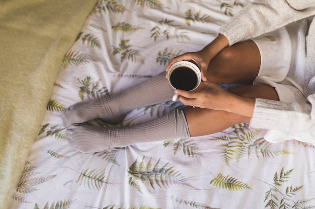 Top view of a teenage girl sitting on bed holding coffee cup