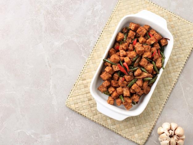 Top view tempe orek 또는 볶음 템페, 인도네시아 전통 요리인 템페로 만든 간장 또는 야자 설탕이 추가되었습니다. 가끔 고추를 넣어 맵게 만드세요. 복사 공간