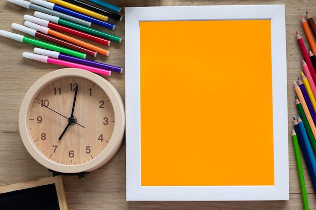 Top view of template white frame mock up with colorful stationary and clock