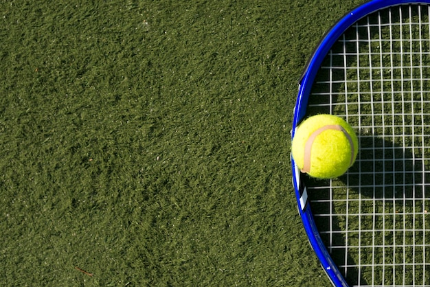 Top view tennis ball and racket with copy space