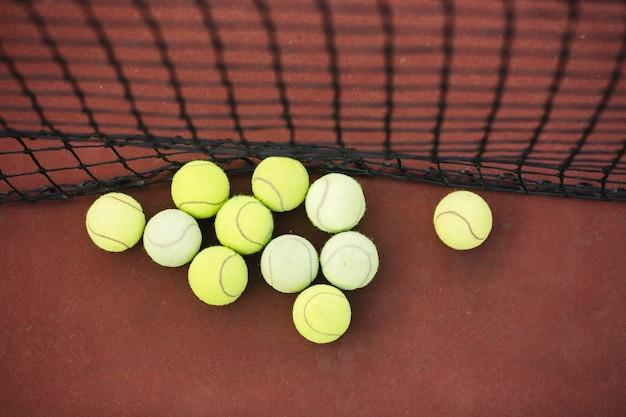 Top view tennis balls beside net on field