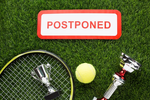 Top view tennis elements arrangement with postponed sign
