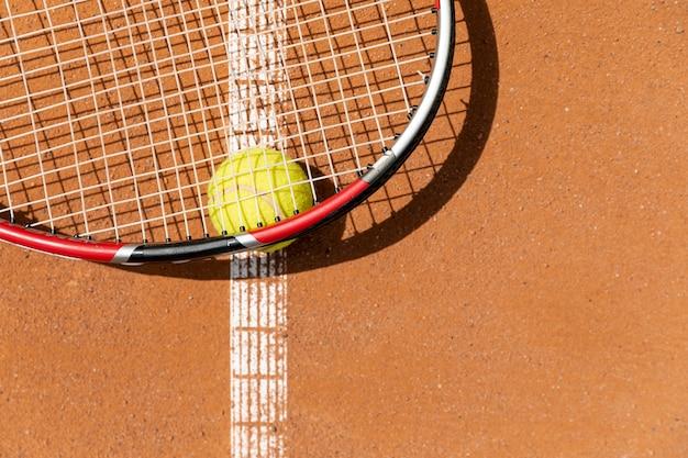 Top view tennis racket over ball
