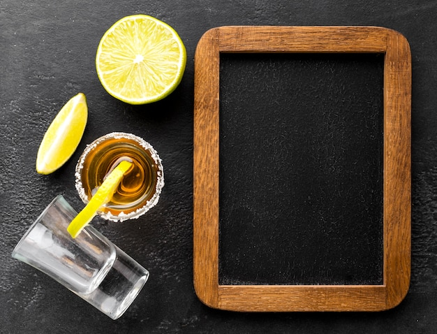 Top view tequila shot and lime slices with blank blackboard