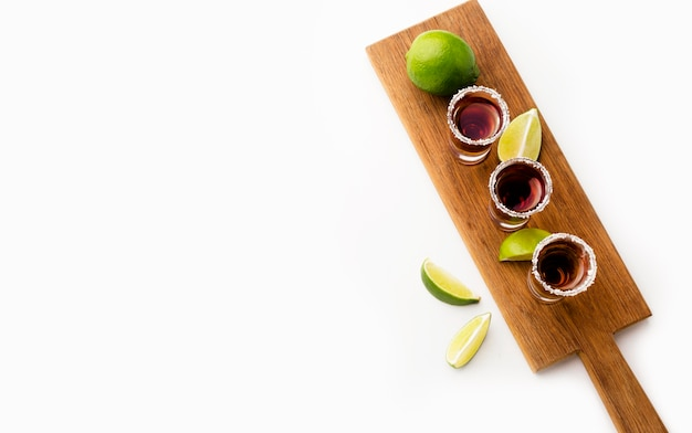 Top view tequila shots with lime slices and copy-space