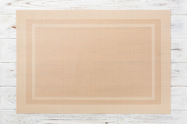 Top view of textile brown mat for dinner on wooden background with copy space