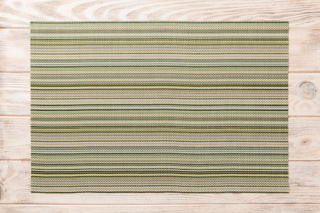 Top view of textile green mat for dinner on wooden background with copy space