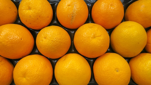 Top view texture of fresh oranges put in box ready to sell in super market, background