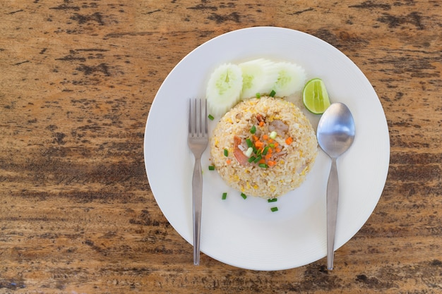 Top view of thai fried rice with prawns on a wooden table.