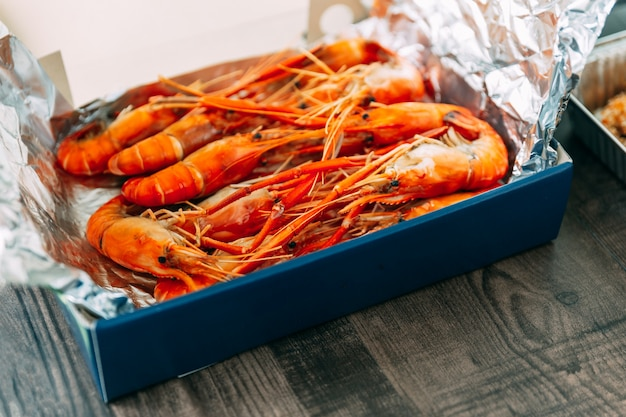 Top view of thai grilled prawns (shrimps) in the shell in paper box that wrap with foil paper.