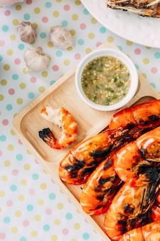 Top view of thai grilled prawns (shrimps) in the shell and without shell in wooden plate served with thai style spicy sauce.