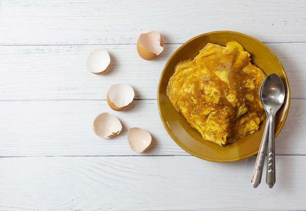上面図タイのオムレツまたは目玉焼きをスプーンで茶色のセラミック皿に少し焦がした